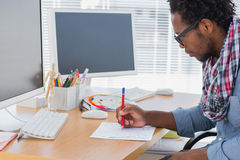 Handsome designer drawing something with a red pencil Stock Image
