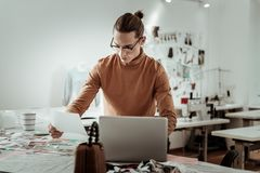 Handsome designer from a fashion studio working on a laptop. Different styles. Handsome designer from a fashion studio wearing a brown garment working on a stock photos