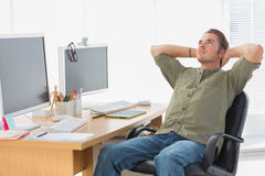 Handsome designer leaning back at his desk Royalty Free Stock Photo