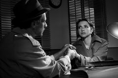 Handsome detective comforting a young scared woman Royalty Free Stock Image