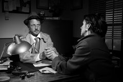 Handsome detective comforting a young scared woman Royalty Free Stock Photo