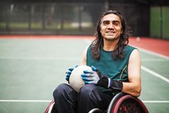Disabled rugby player. Handsome determined disabled rugby player in a wheelchair practicing Stock Image