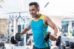 Handsome determined young man exercising with dumbbells in a mod Royalty Free Stock Photos