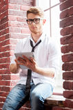 Handsome with digital tablet. Handsome young man in shirt and tie working on digital tablet and looking at camera while sitting at the window sill Royalty Free Stock Photography