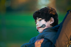Handsome disabled boy in wheelchair at park, quiet expression Royalty Free Stock Photos