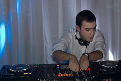 Handsome disc jockey mixing music at a deck stock photo