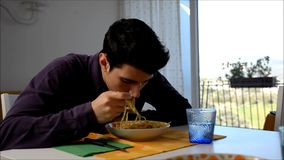 Handsome distracted young man sitting enjoying his meal of spaghetti stock footage