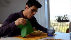 Handsome distracted young man sitting enjoying his meal of spaghetti stock video