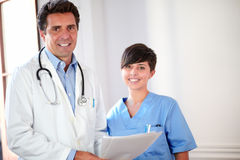 Handsome doctor and beautiful nurse smiling Stock Photography