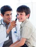 Handsome doctor examining little boy's ears Stock Photography