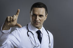 Handsome doctor gesturing on a grey background Royalty Free Stock Photos