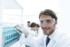 Close-up of a happy male scientist wearing safety glasses. Handsome doctor in gloves and mask holding a test tube, looking at the camera and smiling while Royalty Free Stock Image