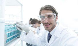 Close-up of a happy male scientist wearing safety glasses. Handsome doctor in gloves and mask holding a test tube, looking at the camera and smiling while Stock Image
