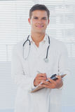 Handsome doctor holding a clipboard Stock Photos