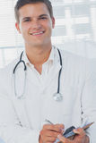 Handsome doctor holding pen Royalty Free Stock Images