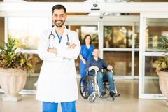 Handsome doctor in the hospital entrance. Portrait of an attractive Hispanic doctor standing in the hospital entrance with a patient in a wheelchair in the Stock Images