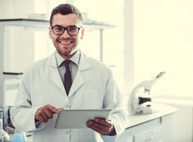 Handsome doctor in laboratory. Handsome medical doctor in white coat is using a digital tablet, looking at camera and smiling while standing in laboratory Stock Photos