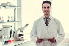 Handsome doctor in laboratory. Handsome medical doctor in white coat is using a digital tablet, looking at camera and smiling while standing in laboratory Royalty Free Stock Photography