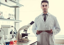 Handsome doctor in laboratory. Handsome medical doctor in white coat is using a digital tablet and looking at camera while working in laboratory Royalty Free Stock Images