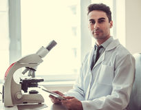 Handsome doctor in laboratory. Handsome medical doctor in white coat is using a digital tablet and looking at camera while working in laboratory Royalty Free Stock Image