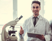 Handsome doctor in laboratory. Handsome medical doctor in white coat is using a digital tablet, showing Ok sign, looking at camera and smiling while working in Stock Photo