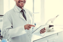 Handsome doctor in laboratory. Handsome medical doctor in white coat is using a digital tablet and smiling while standing in laboratory Stock Photography