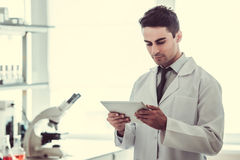 Handsome doctor in laboratory. Handsome medical doctor in white coat is using a digital tablet while working in laboratory Royalty Free Stock Photos