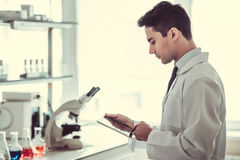 Handsome doctor in laboratory. Handsome medical doctor in white coat is using a digital tablet while working in laboratory Royalty Free Stock Photography