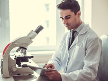 Handsome doctor in laboratory. Handsome medical doctor in white coat is using a digital tablet while working in laboratory Royalty Free Stock Photo