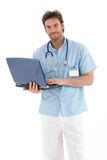 Handsome doctor with laptop smiling Royalty Free Stock Image