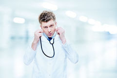 Handsome doctor listening with a stethoscope Stock Photography