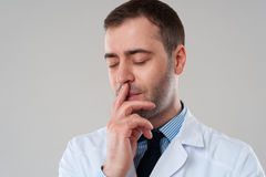Handsome doctor male with hand on face Royalty Free Stock Photos