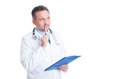 Handsome doctor or medic holding clipboard and thinking Stock Photo