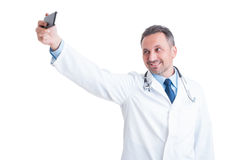 Handsome doctor or medic taking a selfie with smartphone Royalty Free Stock Image