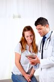 Handsome doctor and a patient looking to tablet PC Royalty Free Stock Images