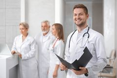 Handsome doctor posing, group of therapists standing behind. royalty free stock photos