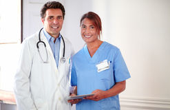 Handsome doctor and pretty nurse looking at you Stock Photos