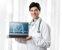 Handsome Doctor showing laptop with heartbeat. On screen royalty free stock images