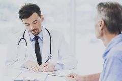 Handsome Doctor with Stethoscope Writes Notes. Royalty Free Stock Photo