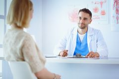 Handsome doctor is talking with young female patient and making notes while sitting in his office royalty free stock photo