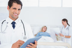 Handsome doctor using digital tablet Stock Images