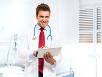 Handsome doctor using a tablet Stock Photo