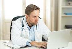 Handsome doctor working on medical expertise and searching information on laptop at hospital office. Portrait of successful attractive doctor in white coat stock images