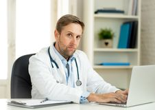 Handsome doctor working on medical expertise and searching information on laptop at hospital office. Portrait of successful attractive doctor in white coat royalty free stock images