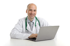 Handsome doktor sitting at a desk with laptop Royalty Free Stock Image