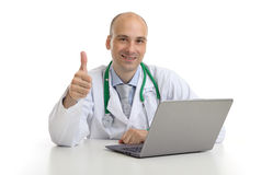 Handsome doktor sitting at a desk with laptop Stock Photography