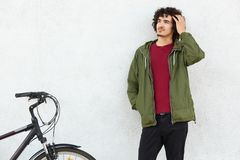 Handsome dreamy male cyclist has curly hair, dressed in casual green anorak, keeps hand in pocket, rides bicycle, concentrated. Aside, isolated over white stock photos