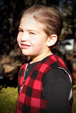 Sweet Lil Country Boy. A handsome young country boy stands in the sunshine squinting with hair all slicked down, wearing a red plaid vest.  Shallow depth of Stock Images