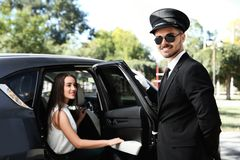 Handsome driver opening car door. For young businesswoman. Chauffeur service stock image