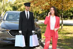 Handsome driver with shopping bags and young businesswoman near car royalty free stock photography